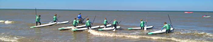 Kinder beim Surfen am Strand in Südholland